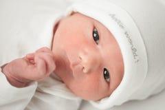 一个白色帽子的面孔婴孩 图库摄影