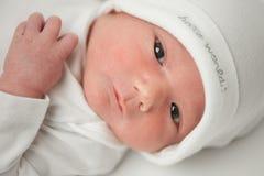 一个白色帽子的面孔婴孩 库存图片