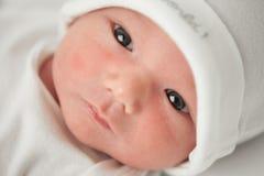 一个白色帽子的面孔婴孩 库存照片