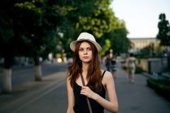 一个白色帽子的年轻美丽的妇女在城市在晚上 免版税库存图片