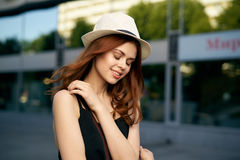 一个白色帽子的年轻美丽的妇女走沿一条街道的在一个城市在夏天 图库摄影