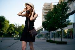 一个白色帽子的年轻美丽的妇女走沿一条街道的在城市 库存图片