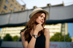 一个白色帽子的年轻美丽的妇女走沿街道的 库存照片