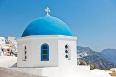 一个白色教会的蓝色圆顶有破火山口峭壁的在背景中, Oia村庄,圣托里尼海岛 图库摄影