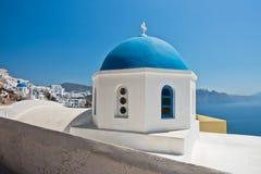 一个白色教会的蓝色圆顶有破火山口峭壁的在背景中, Oia村庄,圣托里尼海岛 免版税库存图片