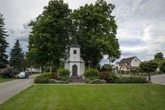 一个白色教堂在大树下在一个小村庄的中心 库存图片