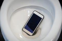 一个白色智能手机滴下了入马桶 免版税库存照片