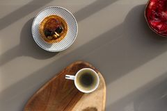 一个白色杯子浓咖啡用在木背景的与坚果和草莓的牛奶和蛋糕在灰色背景 免版税库存图片