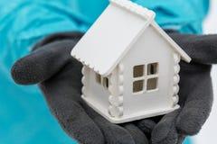 一个白色玩具房子的模型在戴着黑暗的手套的一个人的手上在冬天 免版税图库摄影