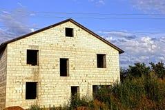 一个白色砖房子的建筑在反对天空和云彩的庭院里 库存照片