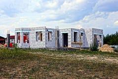 一个白色砖房子的建筑草的反对天空 免版税库存照片