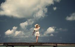 一个白色礼服和帽子的一个女孩在桥梁站立 马尔代夫 海岛 热带 库存图片