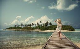 一个白色礼服和帽子的一个女孩在桥梁站立 马尔代夫 海岛 热带 免版税库存图片