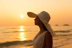 一个白色礼服和草帽的年轻美丽的女孩在tropica 图库摄影