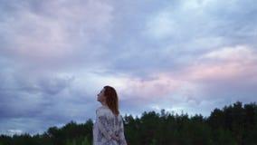 一个白色礼服身分在前景和享用的罕见的发光的自然天空-喜怒无常的冷的日落年轻女人女孩 影视素材