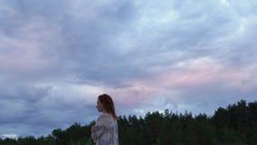 一个白色礼服身分在前景和享用的罕见的发光的自然天空-喜怒无常的冷的日落年轻女人女孩 股票视频