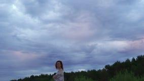 一个白色礼服身分在前景和享用的罕见的发光的自然天空-喜怒无常的冷的日落年轻女人女孩 股票录像