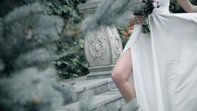 一个白色礼服身分的美女在台阶 妇女拿着在风振翼的一件礼服 股票视频
