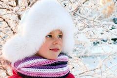 一个白色蓬松帽子的小女孩 免版税库存照片