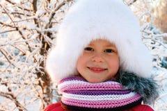一个白色蓬松帽子的逗人喜爱的小女孩 库存图片