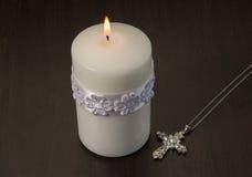 一个白色蜡烛点燃了与在木backgrou的下垂水晶十字架 库存照片