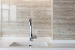 一个白色长方形设计师厨房水槽的细节与镀铬物水龙头的对铺磁砖的墙壁 免版税库存图片