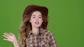 一个皮革帽子的牛仔女孩唱歌入一个减速火箭的话筒 绿色屏幕 慢的行动 股票录像