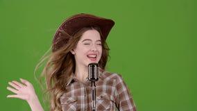 一个皮革帽子的牛仔女孩唱歌入一个减速火箭的话筒 绿色屏幕 股票录像