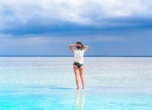 一个盐湖的表面上的一个女孩立场温泉渡假胜地的 海滩的少妇与白色沙子敬佩美丽 免版税库存照片