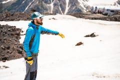 一个盖帽的一名登山家有玻璃和冰块夹子的在一座积雪覆盖的山的背景站立 免版税库存照片