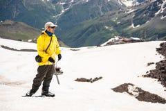 一个盖帽的一名登山家有玻璃和冰块夹子的在一座积雪覆盖的山的背景站立 免版税图库摄影