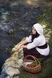 一个盖帽的中世纪女孩在有篮子的河 图库摄影