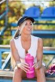 一个盖帽的性感的体育妇女,有一个瓶的在体育场背景的水 被设色的背景秀丽蓝色概念容器装饰性的深度详细资料域充分的仿效宏观自然超出珍珠浅天空 库存图片