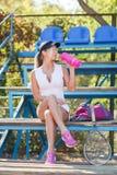 一个盖帽的性感的体育妇女,有一个瓶的在体育场背景的水 被设色的背景秀丽蓝色概念容器装饰性的深度详细资料域充分的仿效宏观自然超出珍珠浅天空 库存照片