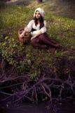 一个盖帽的无辜的中世纪女孩在有断枝的一条河 库存照片