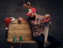 一个盖帽的有胡子的人有鹿垫铁的举行手锯和看a 免版税图库摄影