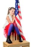 一个相当小女孩坐有一面美国国旗的一个箱子 免版税库存照片