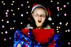 一个相当小女孩打开她的圣诞节礼物 免版税图库摄影