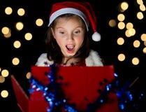 一个相当小女孩打开她的圣诞节礼物 库存照片