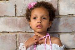 一个相当小女孩混血儿的画象。体贴的夫人 免版税图库摄影