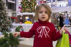 一个相当小女孩的特写镜头画象一件红色毛线衣的有在圣诞节背景的礼物的 商城 免版税库存照片