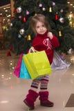 一个相当小女孩的画象一件红色毛线衣的有在圣诞树背景的礼物的 在圣诞节的商城 库存图片