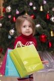 一个相当小女孩的画象一件红色毛线衣的有在圣诞树背景的礼物的 在圣诞节的商城 图库摄影