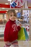 一个相当小女孩的画象一件红色毛线衣的有在圣诞树背景的礼物的 在圣诞节的商城 免版税库存照片