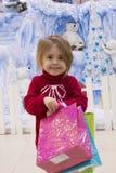 一个相当小女孩的画象一件红色毛线衣的有在圣诞节背景的礼物的在圣诞节的商城 免版税库存图片