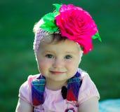 一个相当小女孩的画象有一朵花的在她的头 免版税图库摄影