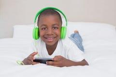 一个相当小男孩使用智能手机的和听的音乐的画象在床 免版税图库摄影