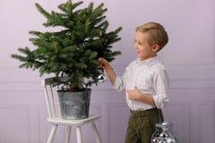 一个相当小男孩,金发,他佩带与银色泡影的一棵圣诞树 免版税库存图片