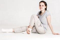 一个相当少妇女孩的画象坐在白色隔绝的地板 免版税库存照片