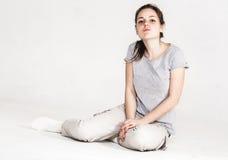 一个相当少妇女孩的画象坐在白色隔绝的地板 库存图片